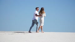 Beautiful young loving couple and walking barefoot in the desert Stock Footage
