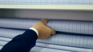Man replacing blue cotton fabrics from a pile in a textiles shop. Stock Footage