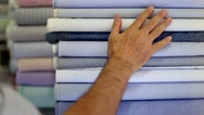 Customer touching blue cotton fabrics in a textiles shop. Stock Footage