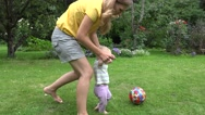 Young mother play with baby girl with ball in summer garden. 4K Stock Footage