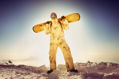 Snowboarder posing on blue sky backdrop in mountains Stock Photos