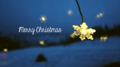 Merry Christmas title and a light flake shape dangling in front of a window. Stock Footage