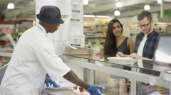 4K Happy worker in supermarket serving customers at the deli counter Stock Footage