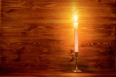 Burning old candle with vintage brass candlestick on wooden background, natur Stock Photos
