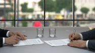 Two businessmen sign documents. Stock Footage