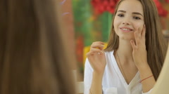 Female beauty, happy mid adult woman putting cream on face skin and smiling Stock Footage