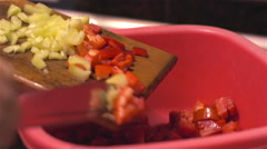 Green and red peppers fall from the cutting Board into bowl Stock Footage