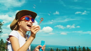 Portrait little hiker child girl 7-8 years old blowing soap bubbles and sitting Stock Footage
