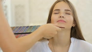 A cute model gets makeup put on before her shoot. Close up shot Stock Footage
