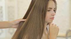 Hairdresser using straightener on beautiful woman hair in hair salon Stock Footage