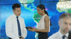 4K Business people talking & looking at large world map graphic. Global business Stock Footage
