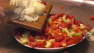 Chopped onion falls from utting Board to vegetables in dish Stock Footage