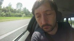 Tired man sleeping on passenger seat of car in motion Stock Footage