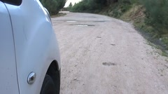 Car going through water puddle on mountain dirt road slow motion 120fps Stock Footage