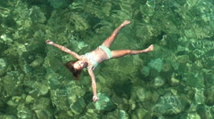 Girl lies on the water in the form of star. Stock Footage