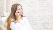 Beautiful young woman talking on mobile phone at home Stock Footage