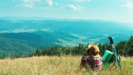 Portrait little hiker girl 7-8 years using binoculars and sitting on grass Stock Footage