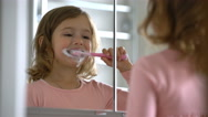Little girl diligently brushing his teeth in the mirror. Stock Footage