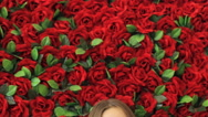 Girl smiling at camera on the background of red roses Stock Footage