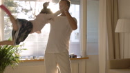 Dad turns and throws up a small daughter on hands in the Sunny room. Slow motion Stock Footage