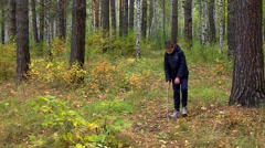 Autumn in the forest - Boy is looking for something in fallen leaves Stock Footage