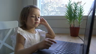 Little girl with interest uses the laptop. Dolly shot. Slow motion. Stock Footage
