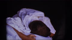 1968: a cute young boy waking up in bed wrapped in white sheets COTTONWOOD Stock Footage