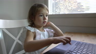 Little girl with interest uses the laptop sitting at the table. Dolly shot. Stock Footage
