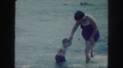 1958: two women tending their children wading in shallow water AMES, IOWA Stock Footage