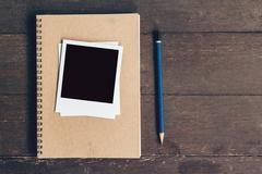 Notebook and pencil with frame photo on wood table background with space Stock Photos