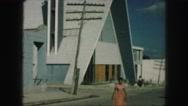 1958: a woman walking across a parking lot with a church behind her AMES, IOWA Stock Footage