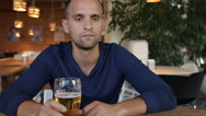 Young businessman drinking beer in cafe Stock Footage