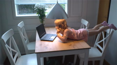 Little girl enthusiastically watching cartoons on a laptop lying on the table. Stock Footage