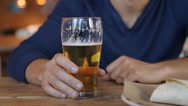 Young man drinking beer in cafe in the city Stock Footage