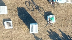 Cyclists doing jump MTB tricks in bicycle HD aerial video. Mountain bike trial Stock Footage