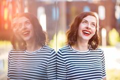 Portrait of a beautiful stylish brunette smiling. golden hour. flare graded Stock Photos