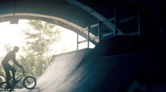 Сyclist doing BMX tricks in bicycle HD slow motion video. Bike rider park ramp Stock Footage