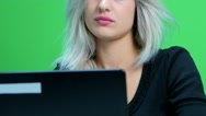 Close up of girl sitting at table and working at a laptop. Green screen studio Stock Footage