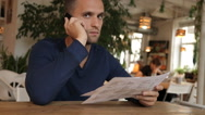 Young man in cafe or restaurant, looking through the menu talking phone Stock Footage
