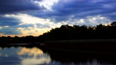 Beautiful cloudscape and sunset breaking through cloud over lake reflection Stock Footage