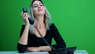 Cute girl in an office talking on the phone with a client. Green screen studio Stock Footage