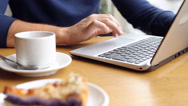 Young man working on modern laptop in cafe Stock Footage