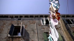 From the bottom shot of wet laundry washed and hung from an ancient building. Stock Footage