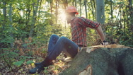One handsome young man with beard and in shirt holding wooden axe walking in Stock Footage