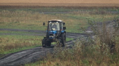 Countryside. a Farmer Riding a Blue Tractor on Durty Rural Road. Early Autumn. Stock Footage