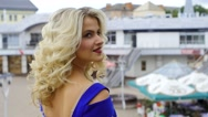 Portrait of a blonde in a blue dress on a background of the city in slow-motion Stock Footage