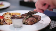 Man cutting a steak on the plate Stock Footage