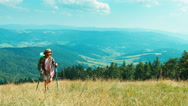 Little hiker girl going up the hill on mountains background at camera Stock Footage