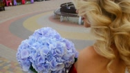 Close-up of blonde woman in a red dress with a bouquet of flowers in their hands Stock Footage