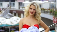 Portrait of blonde woman in a red dress with a bouquet of flowers in their hands Stock Footage